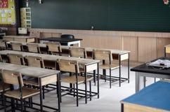Tables et chaises en bois dans une salle de classe vide Photos stock