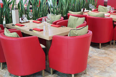 Tables with glasses, soft red armchairs Stock Images