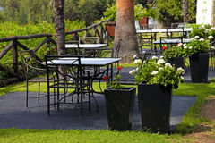 Tables, iron chairs and flower pots in garden (Greece) Royalty Free Stock Image