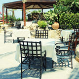 Tables and iron chairs on terrace and beautiful garden, Crete, G Royalty Free Stock Image
