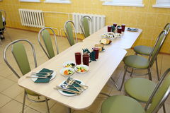 Tables laid for dinner, a municipal medical institution. Yellow and light green colours. Stock Images