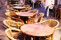 Tables in the outdoor cafe. Group of wicker tables and chairs at an outdoor cafe in the evening Stock Photos