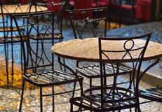 Tables at an outdoor cafe in the rain Stock Images