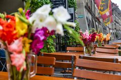 Tables outside the cafe decorated with bouquets of gladioli in Bern, Switzerland royalty free stock photography