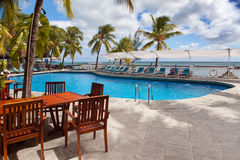Tables at  pool overlooking the sea. Mauritius. Stock Photos