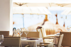 Tables prepared in a restaurant at the beach. Royalty Free Stock Photo