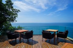 Tables and rattan outdoor armchairs setting on wooden deck and glass balcony with panoramic Andaman ocean sea view, green tree royalty free stock photo
