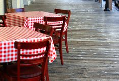 Tables with a red checkered tablecloth. Tables in outdoor seating with a red checkered tablecloth Royalty Free Stock Images