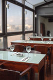 Tables in a restaurant. Set for lunch with glasses and cutlery beside a  large picture windows Stock Images