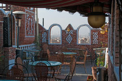 Tables on the roof, view of the Old City of Sana'a, the Saleh Mosque in the fog behind the stone arches, Yemen. The Old City of Sana'a, the oldest continuously stock photos