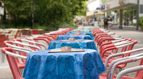 Tables and seats. Red seats and blue tables in a line with ashtrays and menu cards royalty free stock image