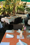 Tables set for dinner at outdoor restaurant. Surrounded by tropical ferns that offer shade while eating Royalty Free Stock Images
