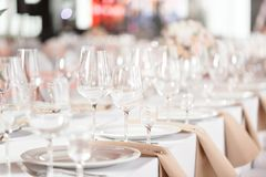 Tables set for an event party or wedding reception. luxury elegant table setting dinner in a restaurant. glasses and. Dishes Stock Photo