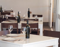 Tables set for lunch or dinner. Bottles of wine are present Stock Photo