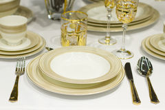 Tables set for meal. Celebratory table setting in golden tone Stock Photography