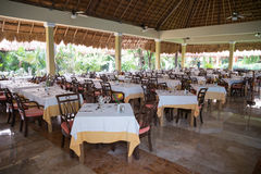 Tables set in a restaurant at a tropical hotel under palm leaf r Stock Photography