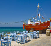 Tables in a tavern near the sea and the red boat Royalty Free Stock Image
