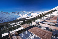Tables on terrace covered by fresh snow near ski slopes on the t Royalty Free Stock Photo