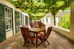 Tables on terrace covered by grape vine Royalty Free Stock Photo