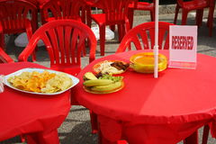 Tables under a red tablecloth with dishes of crisps, fruit and a reserved sign. Royalty Free Stock Photo
