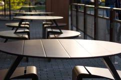 Tables vides d'un café de rue au coucher du soleil Image stock