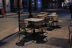 Tables and wicker chairs of an evening street cafe stock image