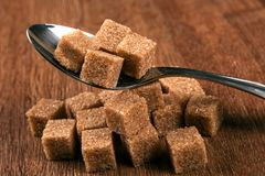 Tablespoon with cubes of brown sugar Stock Photo