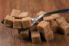 Tablespoon with cubes of brown sugar Royalty Free Stock Images