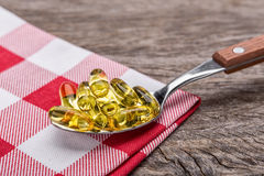 Tablespoon with dietary vitamin E pills. In decorative napkin. Royalty Free Stock Photos
