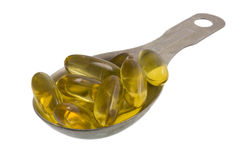 Tablespoon of fish oil capsules Royalty Free Stock Image