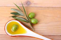 Tablespoon oliwa z oliwek i zielone oliwki - 2 zdjęcia stock
