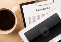 Tablet ПК показывая медиа-проигрыватель на экране с чашкой кофе дальше Стоковые Изображения RF