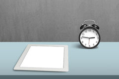 Tablet and alarm clock on table Stock Photos