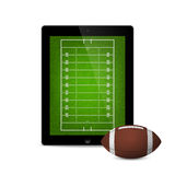 Tablet with american football ball and field on the screen. Royalty Free Stock Photo