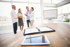 Free Tablet And Planner In Front Of Talking Business People Stock Photography - 58186632