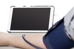 Tablet angeschlossen an einen Blutdruck-Monitor in einer Klinik Lizenzfreie Stockfotos