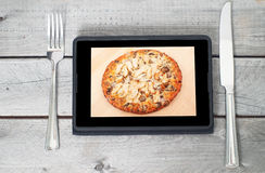 Tablet with an appetizing chicken pizza Stock Image