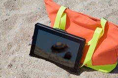 Tablet auf dem Sand im Sonnenlicht Lizenzfreie Stockfotografie