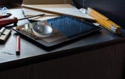 Tablet auf einem dunklen Schrank umgeben durch Werkzeuge in einem schmutzigen Keller Stockfotos