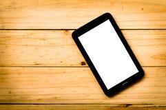 Tablet auf hölzernem Hintergrund im warmen Ton Lizenzfreies Stockfoto