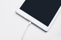 Tablet-Aufladung lokalisiert auf weißem Hintergrund stockfotografie
