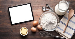 Tablet Baking Food Background. A computer tablet with various baking ingredients and utensils on a warm wood background Royalty Free Stock Photos