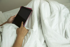 Tablet on bed Stock Images