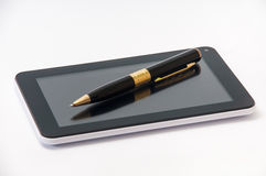 Tablet with a black ballpoint pen on the screen Stock Photography