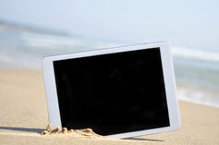Tablet with a black blank space in the screen, in the sand of a Royalty Free Stock Photography