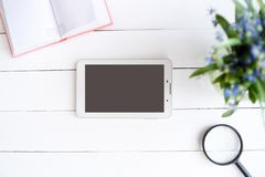 Tablet with black empty screen. Notebook, magnifier and flowers on table.  stock photo