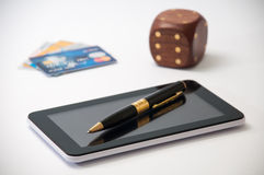 Tablet with a black pen, wooden dice and credit cards in the bac Stock Photos