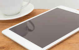 Tablet with blank black screen on wooden table with coffee cup Stock Image