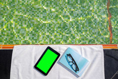Tablet with blank screen and blue book with glasses lying on white towel on the poolside. Tablet with blank green screen and blue book with glasses lying on Royalty Free Stock Images
