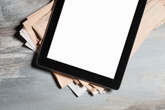 Tablet with blank screen and newspapers Royalty Free Stock Photos